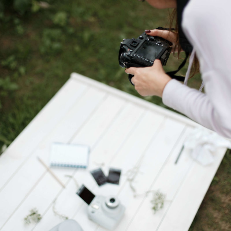 Photographer taking picture of a flat lay for visual effect on how to write a holiday gift guide