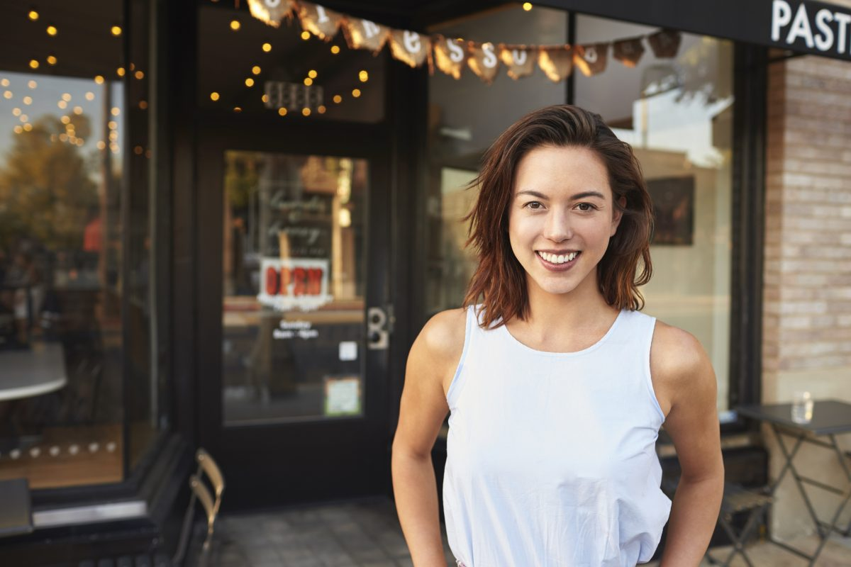 woman standing outside her business wondering if she should start a business blog