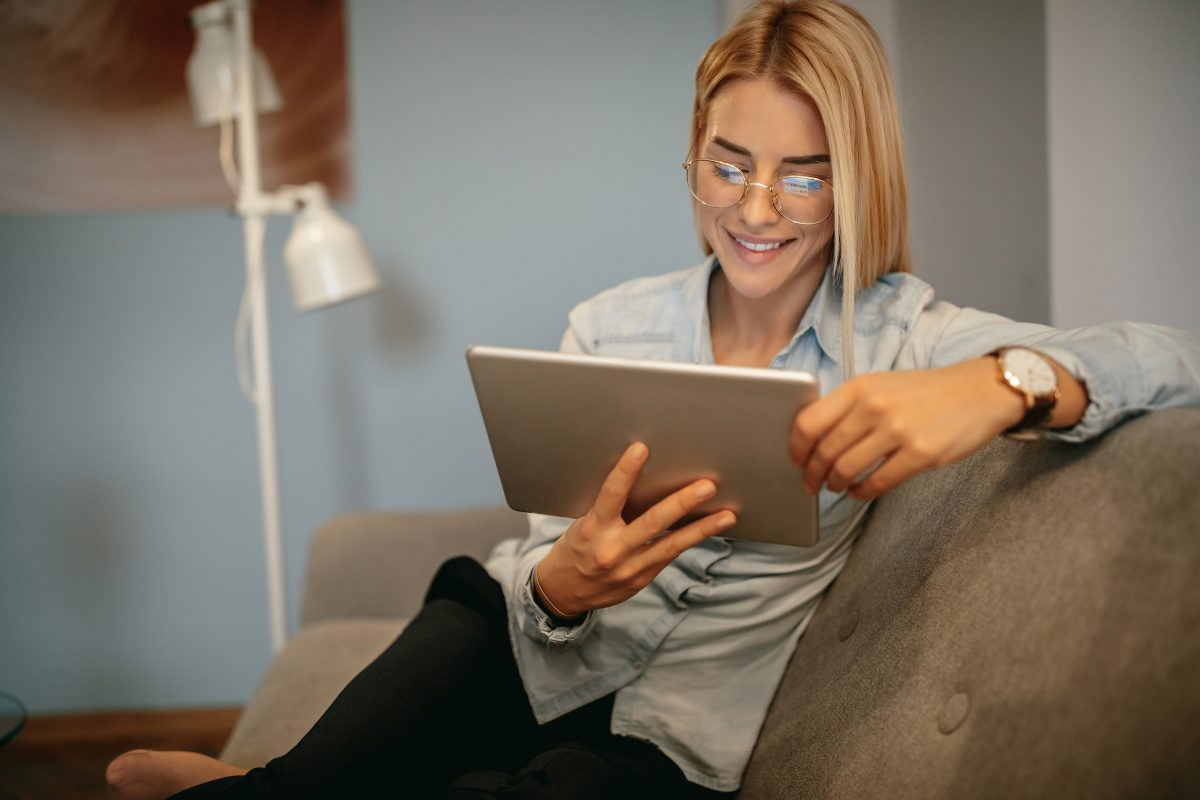 Woman sitting at home reading a blog on her tablet